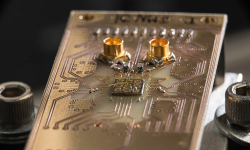 A quantum processor semiconductor chip connected to a circuit board.
